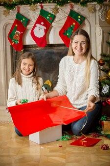 Gelukkige vrolijke dochter en moeder wikkelen trui in papier op kerstavond