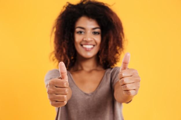 Gelukkige vrolijke donkerbruine vrouw die duim tonen en geïsoleerd glimlachen