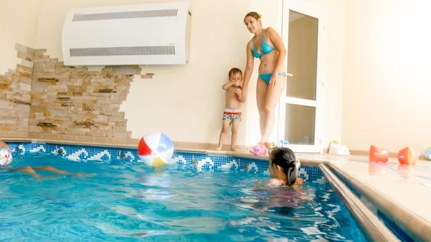 Gelukkige vrolijke familie die plezier heeft in het zwembad