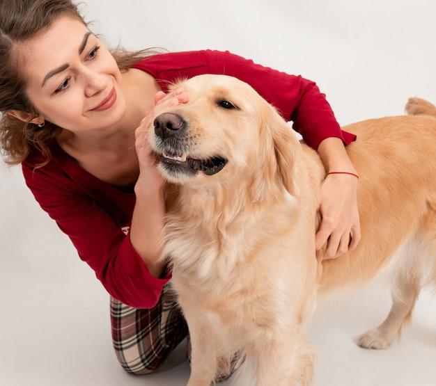 Gelukkige vrolijke glimlachvrouw die en met haar hond op bed thuis spelen koesteren