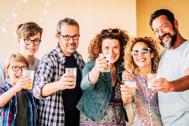 Gelukkige vrolijke groep blanke mensen van gemengde generatie en leeftijden hebben plezier samen rammelend en roosteren om samen te vieren - concept van feest en vriendschap voor volwassenen en tieners