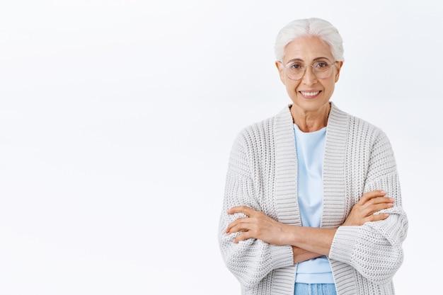 Gelukkige vrolijke grootmoeder die op familie wacht, vest over blouse draagt, warm wordt en een bril, kruisarmen op de borst, casual pose, vrolijk glimlachend voor kleinkinderen zorgend