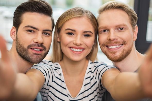 Gelukkige vrolijke jonge mensen die samen staan en naar je kijken terwijl ze een foto maken