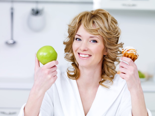 Gelukkige vrolijke jonge mooie vrouw met groene appel en zoete koekzitting in de keuken