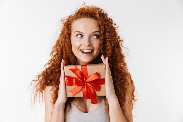 Gelukkige vrolijke jonge roodharige krullende vrouw met verrassingsdoos cadeau.