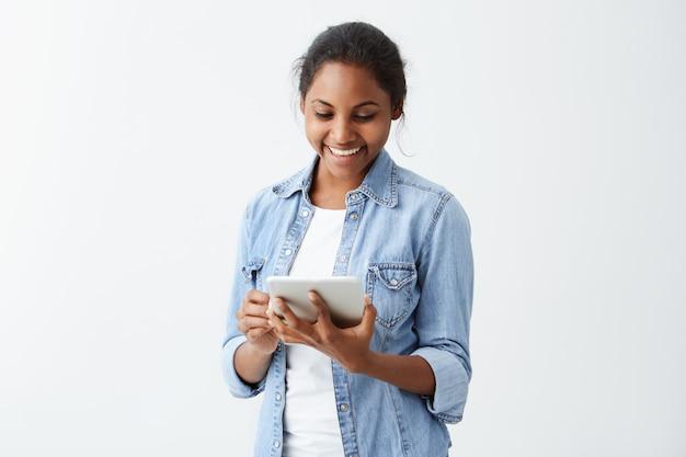 Gelukkige vrolijke jonge vrouw die haar donker haar in broodje dragen die op het scherm van tablet in haar handen kijken die zich bij positief nieuws met blije en charmante glimlach verheugen.
