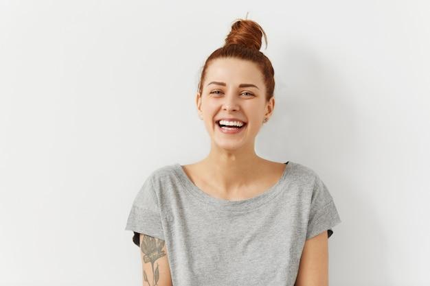 Gelukkige vrolijke jonge vrouw die haar rood haar in broodje draagt, dat blije en charmante glimlach kijkt