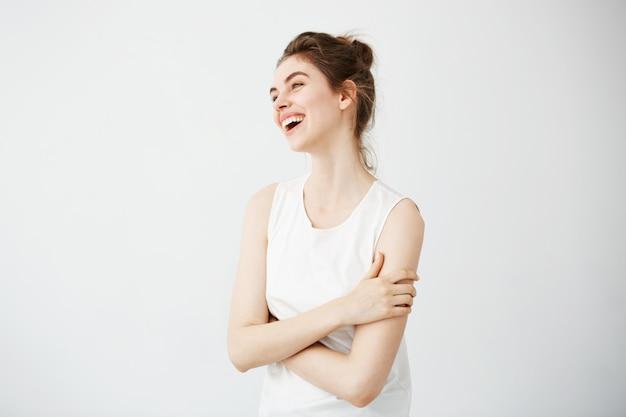 Gelukkige vrolijke jonge vrouw met broodje het glimlachen het lachen. gekruiste armen.