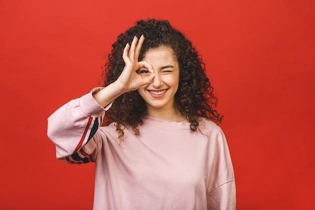 Gelukkige vrolijke jonge vrouw met krullend haar die zich bij positief nieuws verheugen