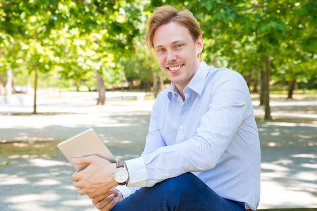 Gelukkige vrolijke jonge zakenman met tablet