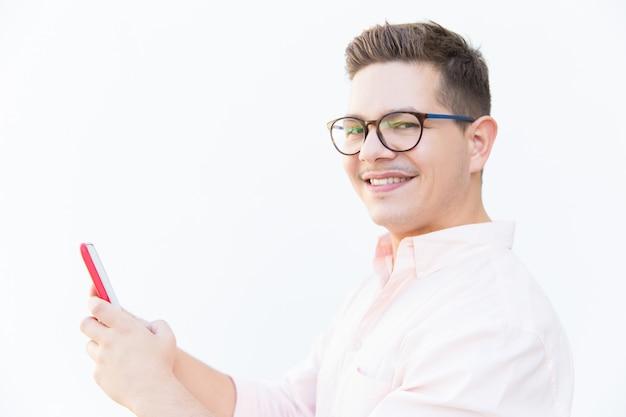 Gelukkige vrolijke kerel die in oogglazen smartphone houden
