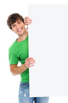 Gelukkige vrolijke kerel kijkt uit van leeg reclamebord op wit