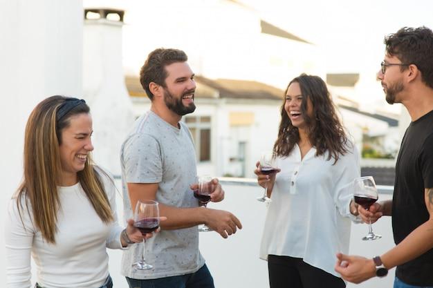 Gelukkige vrolijke mensen die pret hebben en wijn drinken