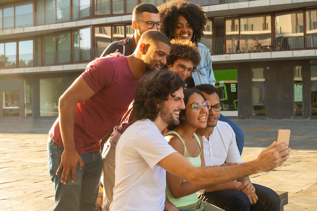 Gelukkige vrolijke mensen tussen verschillende rassen die groep selfie nemen