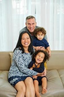 Gelukkige vrolijke multi-etnische familie van vier die thuis op de bank zit en naar de camera kijkt