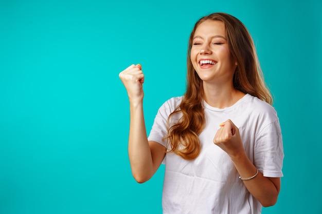 Gelukkige vrolijke opgewonden jonge vrouw die haar succes tegen blauw viert