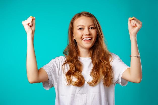 Gelukkige vrolijke opgewonden jonge vrouw die haar succes viert tegen blauwe achtergrond