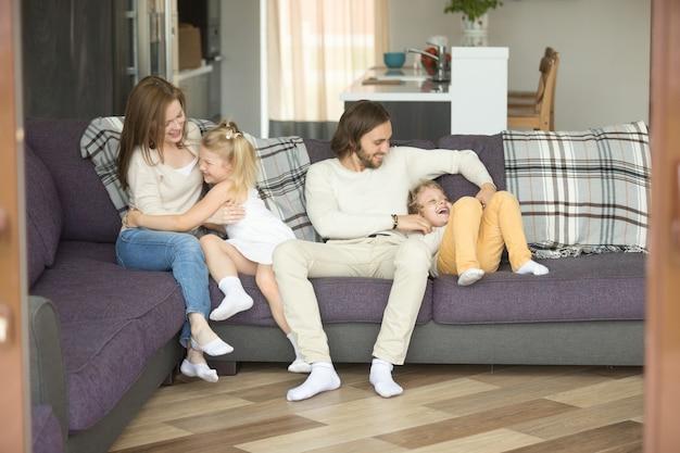 Gelukkige vrolijke ouders die kietelend jonge geitjes spelen die samen thuis lachen