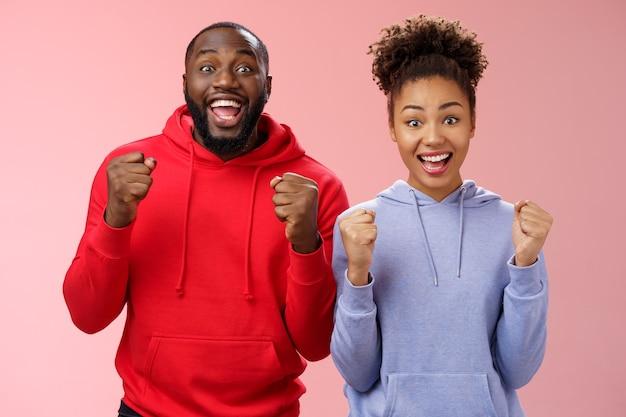 Gelukkige vrolijke twee afro-amerikaanse man vrouw schreeuwen hoera vieren triomfantelijk enorm succes balde vuisten vreugdevol wederzijds doel staande vreugdevol roze achtergrond overwinning gebaar