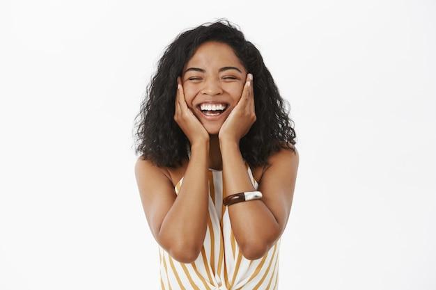 Gelukkige, vrolijke, vriendelijk ogende jonge afro-amerikaanse vrouw die zich verrukt en fris voelt