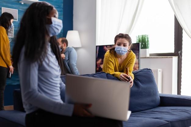 Gelukkige vrolijke vrouw die bierflesje vasthoudt en naar laptop kijkt terwijl ze praat met een afrikaanse vriend in de woonkamer van een appartement met een gezichtsmasker om verspreiding van het coronavirus in de tijd van een wereldwijde pandemie te voorkomen. conceptuele i