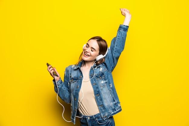 Gelukkige vrolijke vrouw die hoofdtelefoons dragen die aan muziek van het schot van de smartphonestudio luisteren dat op gele muur wordt geïsoleerd