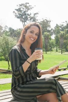 Gelukkige vrolijke vrouw die tablet gebruikt