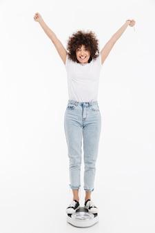 Gelukkige vrolijke vrouw die zich op schalen bevindt