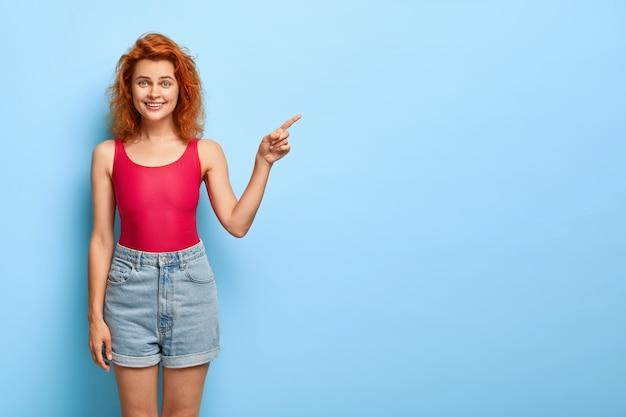 Gelukkige vrolijke vrouw met slank figuur, wijst recht op lege ruimte, adverteert met cool object