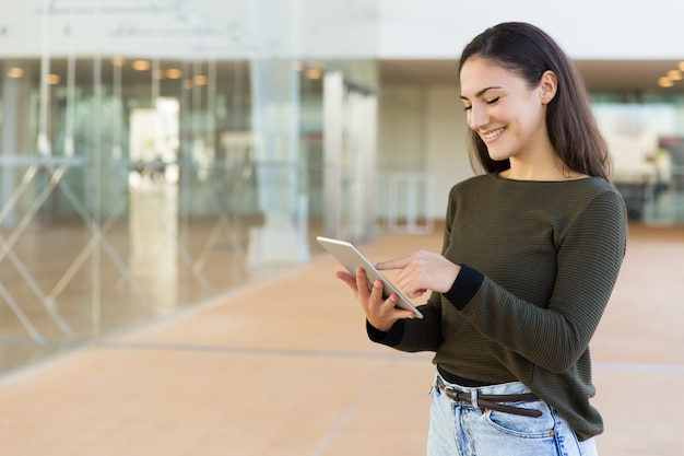 Gelukkige vrolijke vrouw met tablet die internet gebruikt