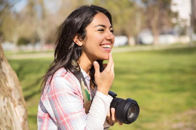 Gelukkige vrolijke vrouwelijke fotograaf met plezier