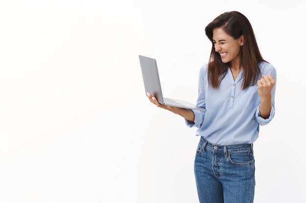 Gelukkige vrolijke vrouwelijke ondernemer ontvangt goed nieuws, viert, houdt laptop vast en verheugt zich over de resultaten, vuistpomp reageert succes, lacht breed gesloten ogen, geniet van de smaakoverwinning, staat op een witte muur