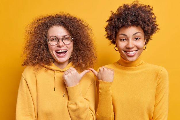 Gelukkige vrolijke vrouwen met gekruld haar van gemengd ras wijzen naar elkaar met een vrolijke uitdrukking en zeggen dat ze dicht bij elkaar staat, nonchalant gekleed geïsoleerd over een gele muur. ik kies jou