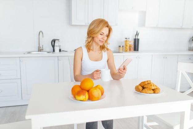 Gelukkige vrouw aan de tafel met fruit en bakken, ontbijt op de keuken.