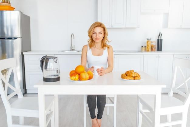 Gelukkige vrouw aan de tafel met fruit en bakken