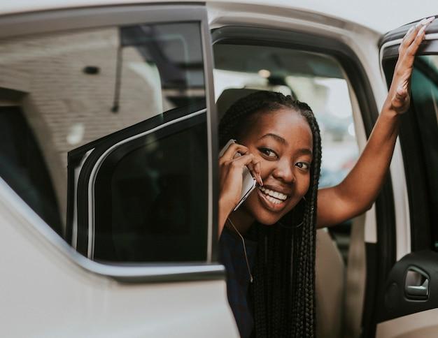 Gelukkige vrouw aan de telefoon in een auto