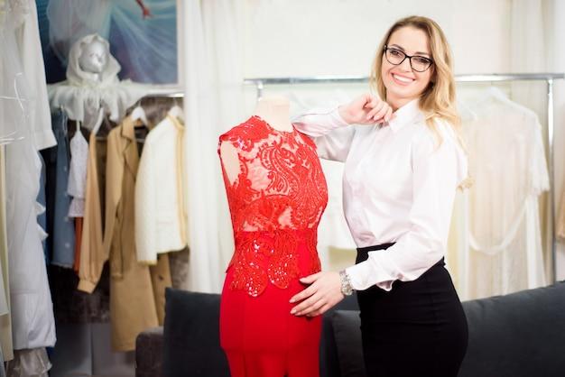 Gelukkige vrouw bedrijfseigenaar in haar kleermakerij. gezellige werkplek, extern werk, bedrijfsconcept.