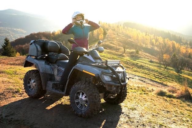 Gelukkige vrouw bestuurder in beschermende helm genieten van extreme rijden op atv quad motor in zomer bergen bij zonsondergang.