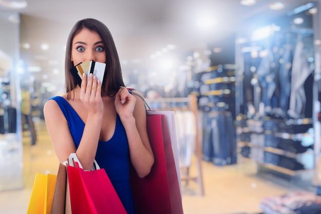 Gelukkige vrouw bij het winkelcentrum met boodschappentassen en creditcard