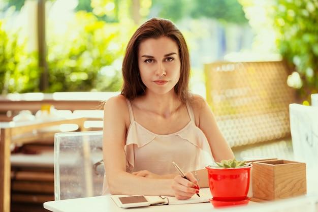 Gelukkige vrouw bij openlucht koffie
