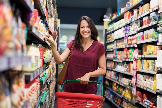 Gelukkige vrouw bij supermarkt