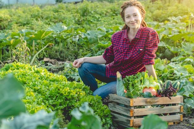 Gelukkige vrouw boer agronoom verzamelt verse groenten