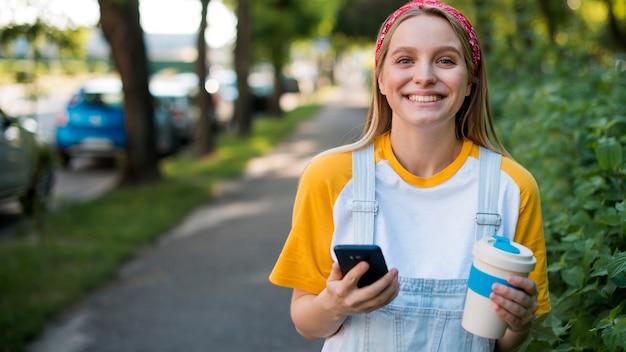 Gelukkige vrouw buiten met smartphone en cup