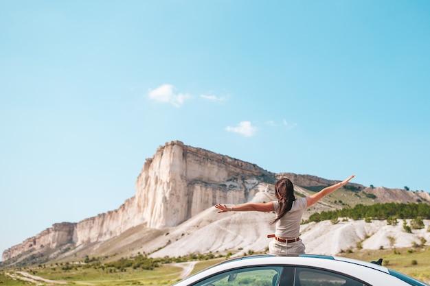 Gelukkige vrouw buiten op de rand van de klif genieten van het uitzicht op de rots van de bergtop