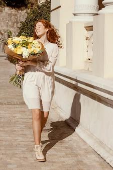 Gelukkige vrouw buitenshuis met boeket van lentebloemen