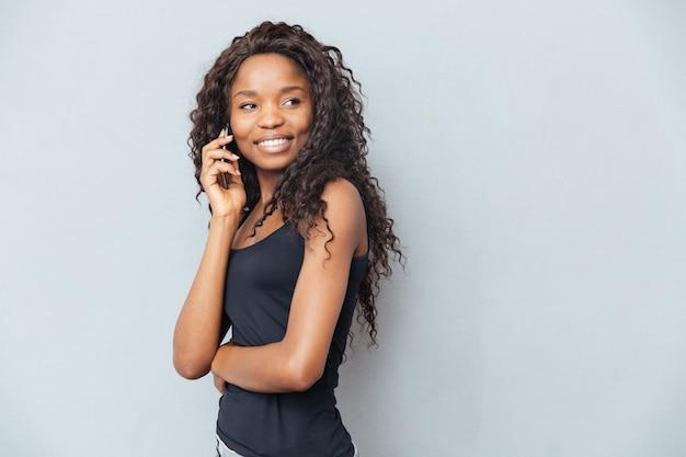 Gelukkige vrouw die aan de telefoon praat en wegkijkt over de grijze muur