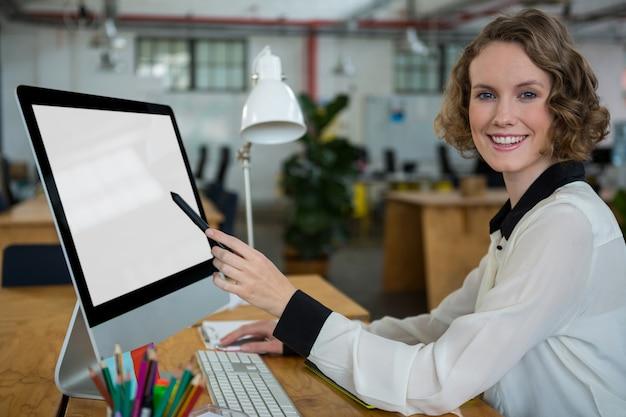 Gelukkige vrouw die aan desktoppc werkt
