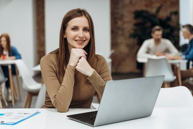 Gelukkige vrouw die aan laptop werkt