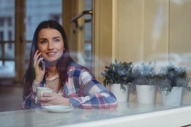 Gelukkige vrouw die aan mobiele telefoon bij koffie luistert