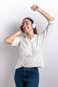 Gelukkige vrouw die aan muziek in hoofdtelefoons luistert